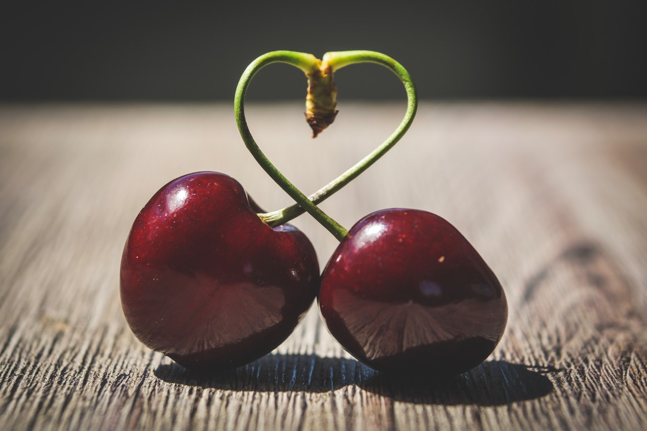 two-red-cherries-on-brown-surface-1394423